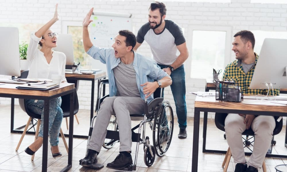 Man in wheelchair giving co-worker a high five.