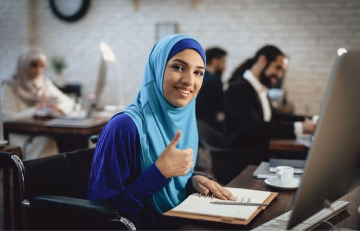 Arab women easily using a website with co-workers in the background.