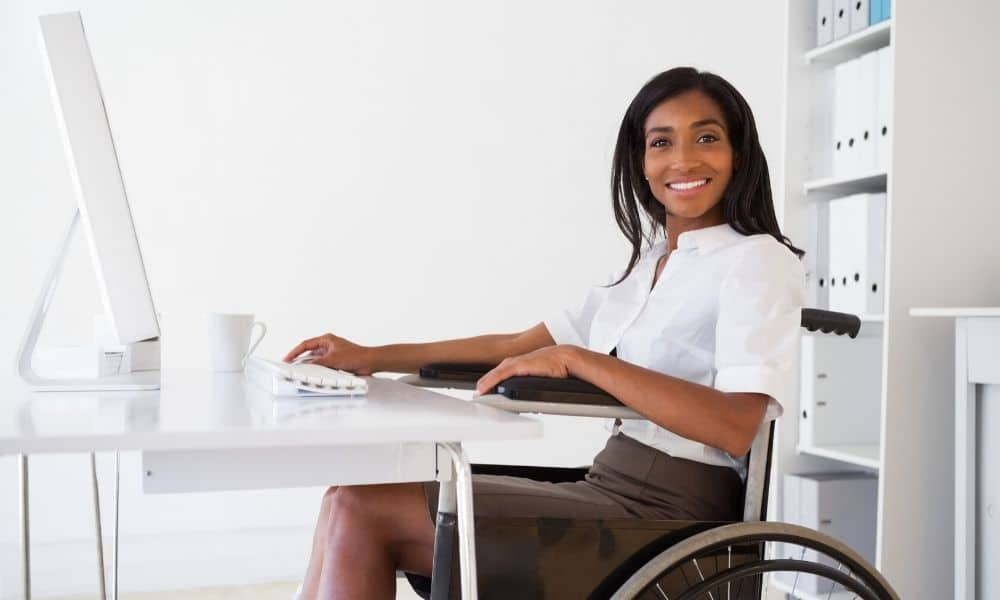 Women smiling using a computer in a wheelchair.